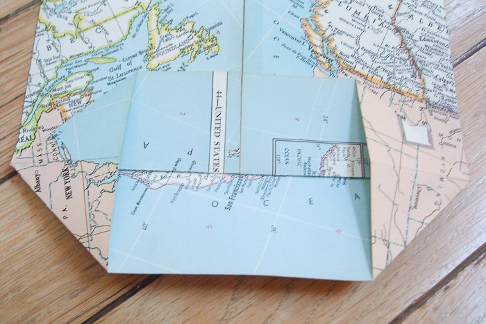 Folding decorative map paper to make a homemade gift bag.