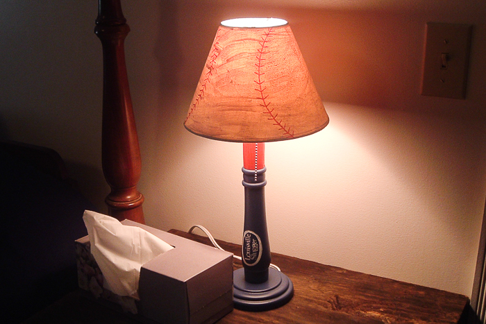 Baseball lamp lit up on a night stand.