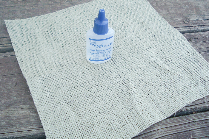 Using fray check on a burlap sheet, preparing to make our burlap throw pillow