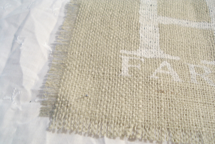 Sewing a piece of burlap to white fabric.