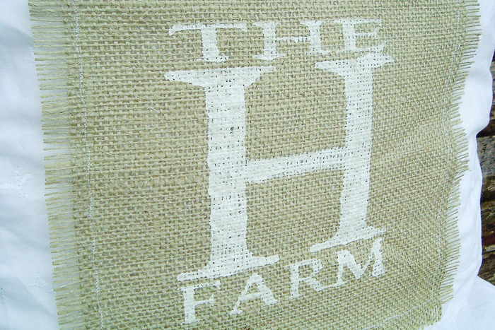 Farm monogram on a burlap pillow attached with a simple stitch along the edges of the burlap