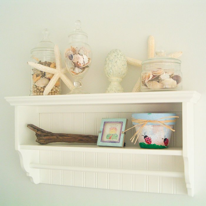 Shelf in a beach themed bathroom with starfish and seashells.