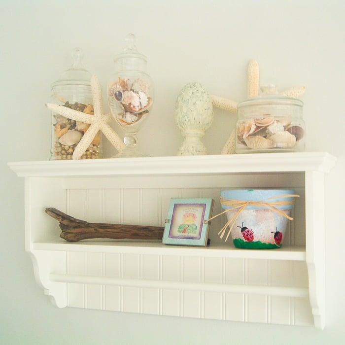 Shelf in a beach themed bathroom with starfish and seashells.