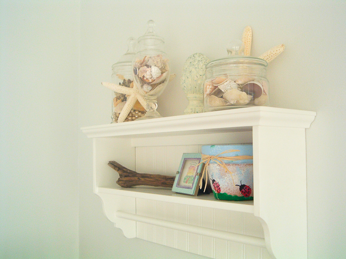 Coastal themed bathroom decor on a shelf including starfish and shells.