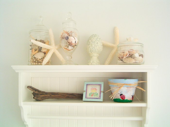White shelf in a beach themed bathroom with starfish and seashells.
