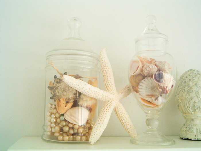 Beach theme bathroom decor including apothecary jars with shells.