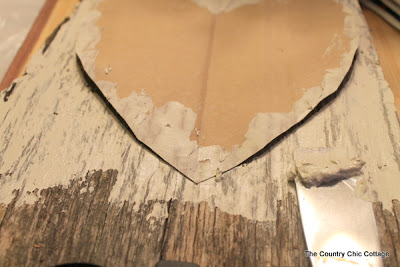 Painting heart shape with white paint onto barn wood
