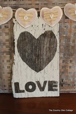 "Wooden sign painted white with heart and word ""love"""