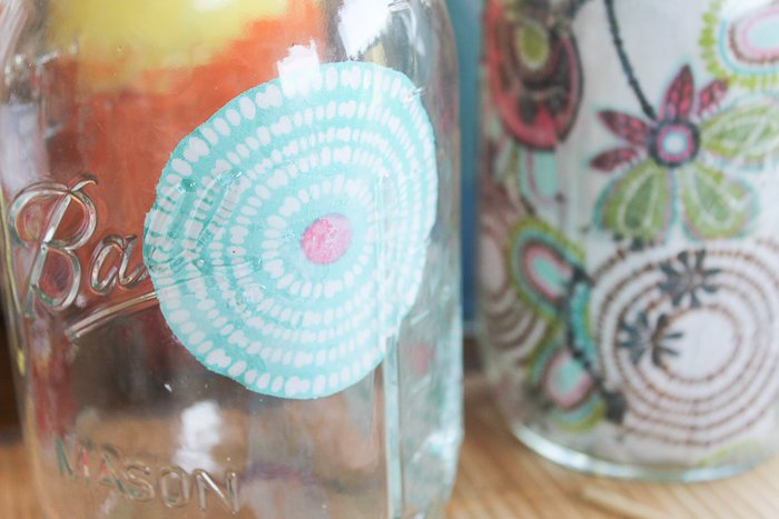 Using decoupage to adhere floral fabric cutouts to the inside of a mason jar