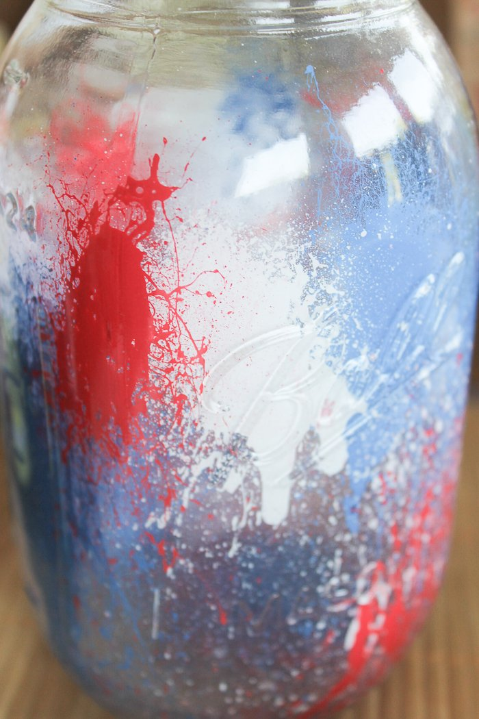 Splattered red, white, and blue paint looks like fireworks inside this painted mason jar!