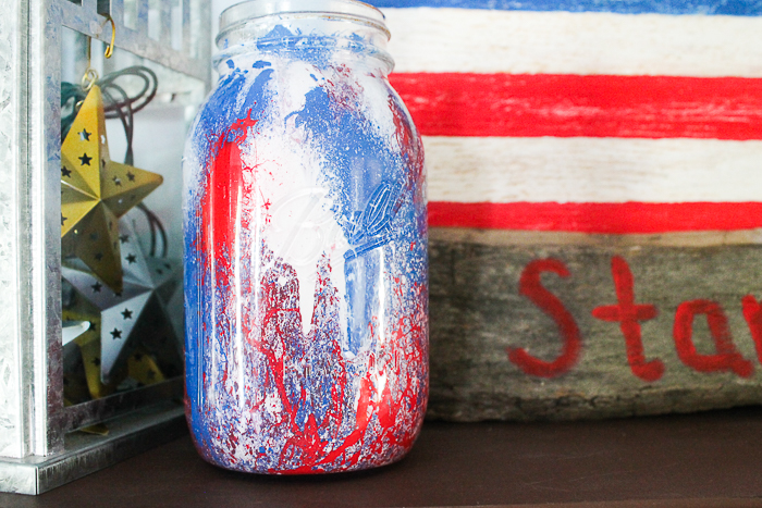 This patriotic mason jar is splattered with red, white, and blue paint