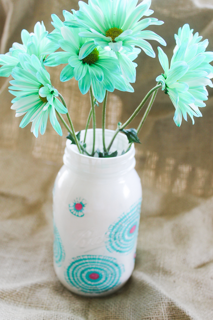 Flowers inside a decorated jar with fabric and paint.