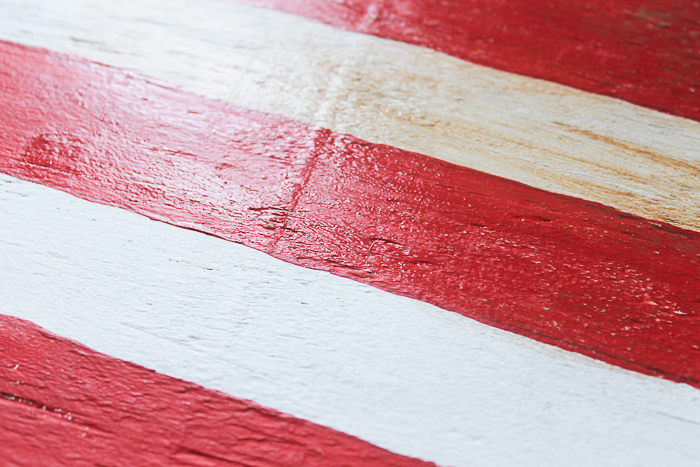 Use the watered down wood stain to distress areas of the painted wooden American flag