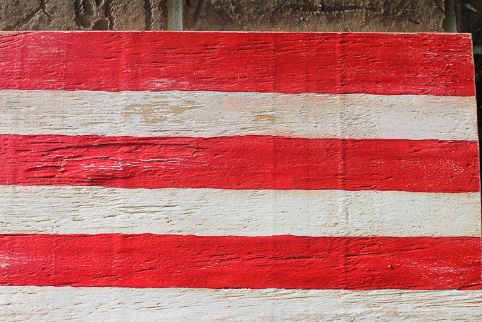 The distressed effect on this Wooden Painted American flag is made with a watered down wood stain