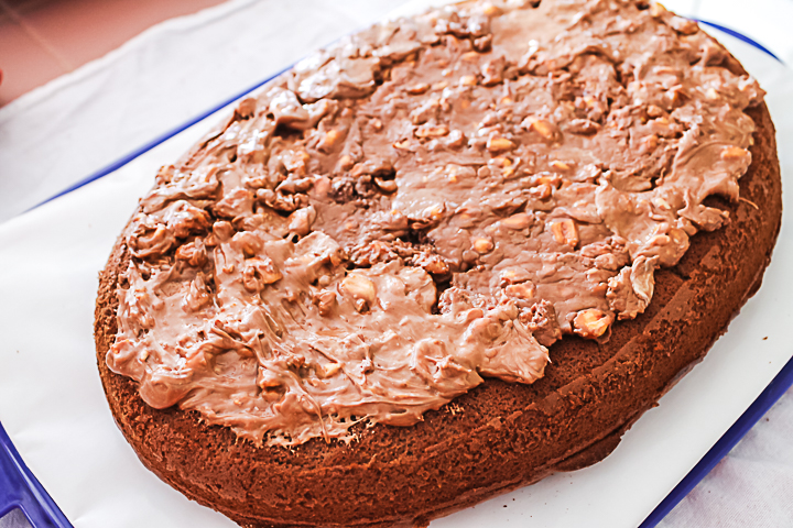 covering a cake with snickers candy