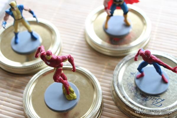 superhero figures being glued to jar lids