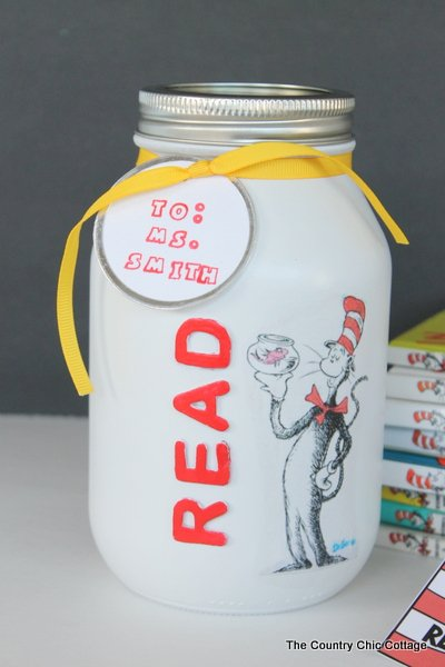 Dr. seuss gift in a jar next to stack of books and homemade bookmark.