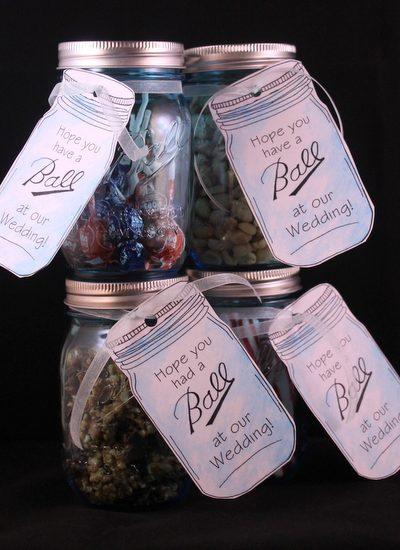 Four mason jar wedding favors with tags