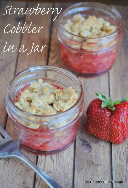 Strawberry Cobbler in a Jar -- get the super simple directions for making your own strawberry cobbler in a jar.  The perfect seasonal dessert!