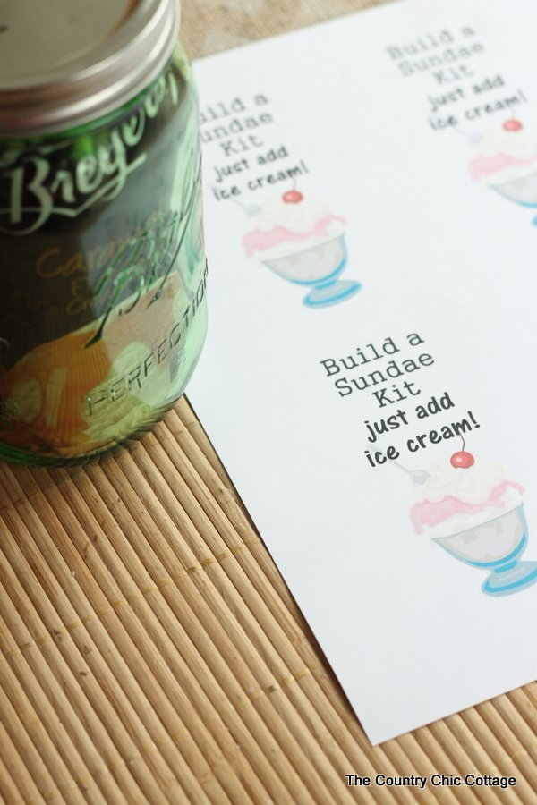 Build a Sundae Kit Gift in a Jar -- fill a mason jar with everything needed for a sundae but ice cream. Includes free printable tags!