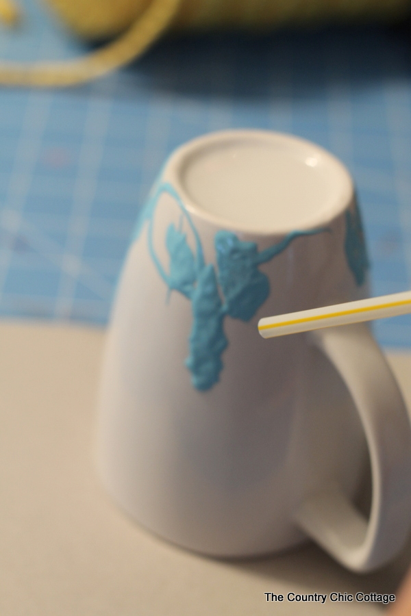 Blowing air through a straw to create a marbled look on a mug
