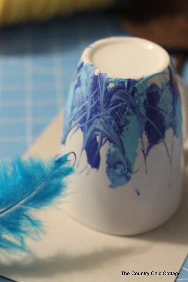 Use a feather to blend blue paint on a white coffee mug
