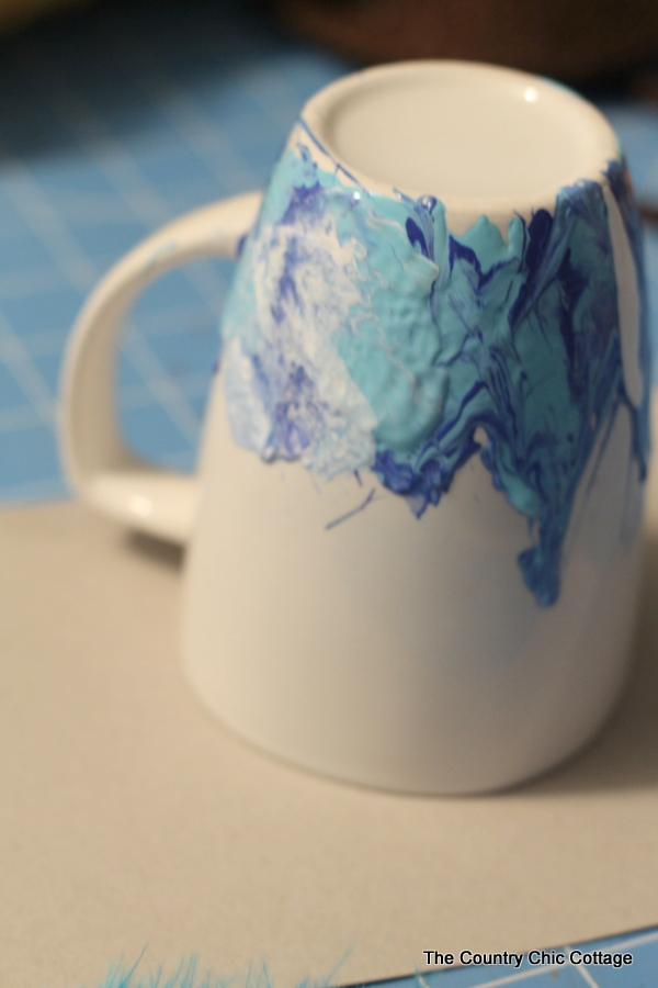 Mixing the white paint into the other blue paints on the white coffee mug