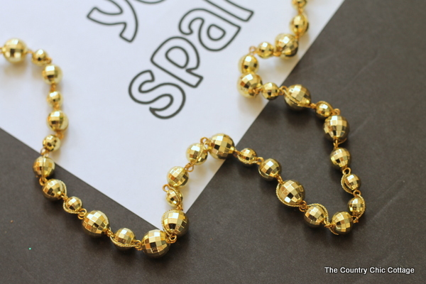 Make this gold ball garland plus print a free coloring page printable and never let anyone dull your sparkle!