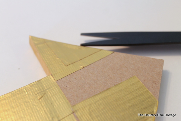 Metallic gold arrow made from cardboard boxes and Duck tape -- get the full instructions here!