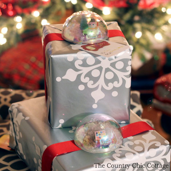 Make these snow globe present toppers for your Christmas gifts! A great addition to holiday presents in place of a traditional bow!