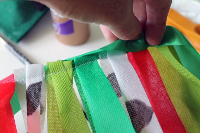 Sewing together the ribbons to make a farm and tractor themed first birthday highchair banner