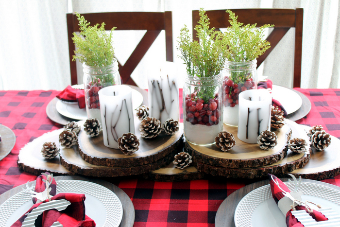 table centerpiece made with wooden rings, candles, christmas mason jars, and pinecones