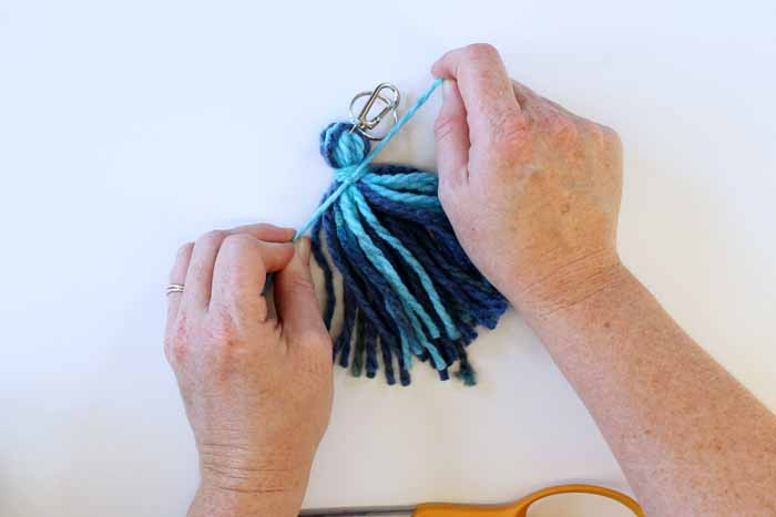 after wrapping the yarn around the tassel several times, tie it securely