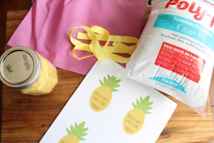 paper with pineapples printed and yellow ribbon with pink fabric on wooden board