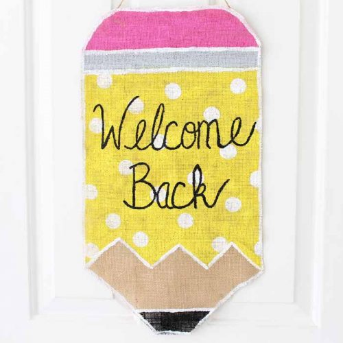 painted burlap pencil wall hanging on white door that says welcome back