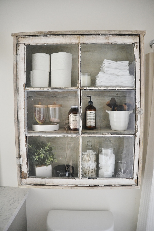 This old rustic window is perfect bathroom storage and I love how vintage it looks!