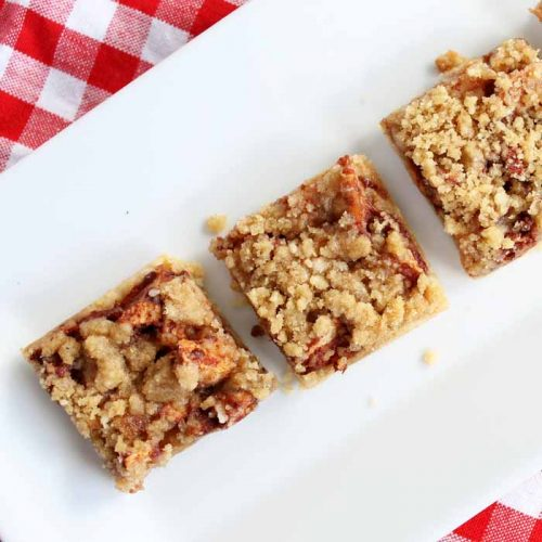 three pieces of apple bars on a white plate with a red checkered tablecloth