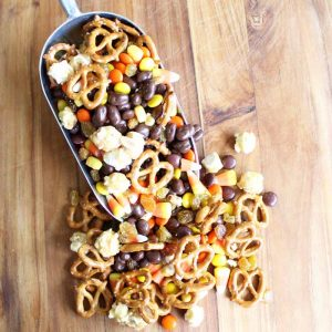 A close up halloween snack mix with a scoop on a wooden table