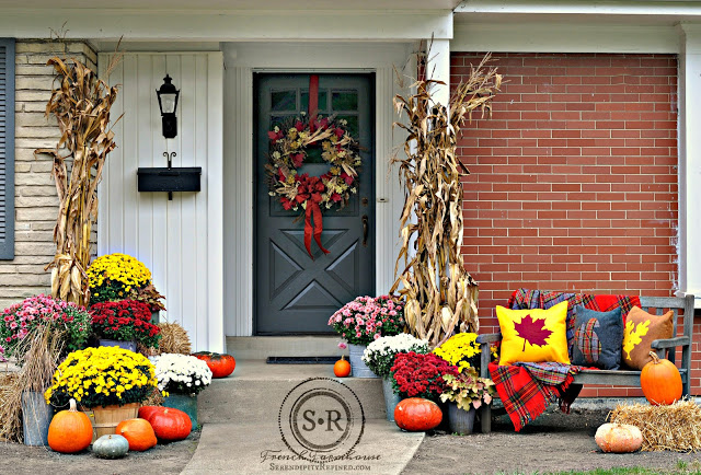 fall porch decor with pumpkins, mums, a wreath and bright colors