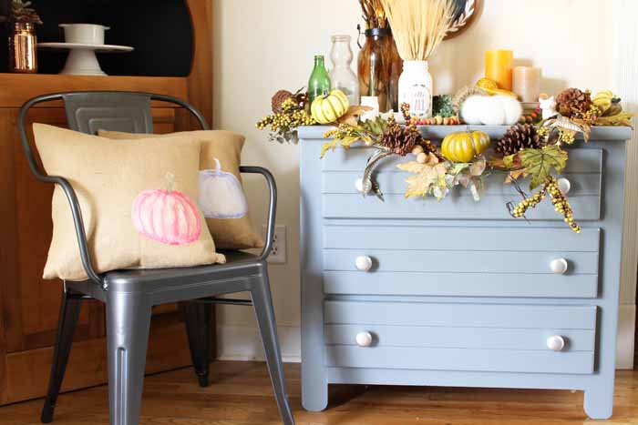 Blue dresser with burlap pillows in galvanized chair with fall display