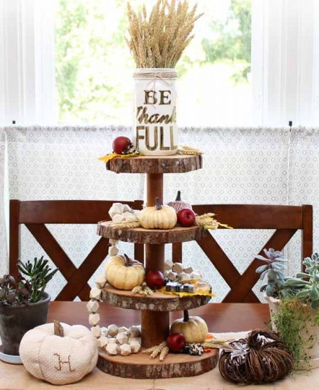 A tiered wood server with fall accessories in front of a window