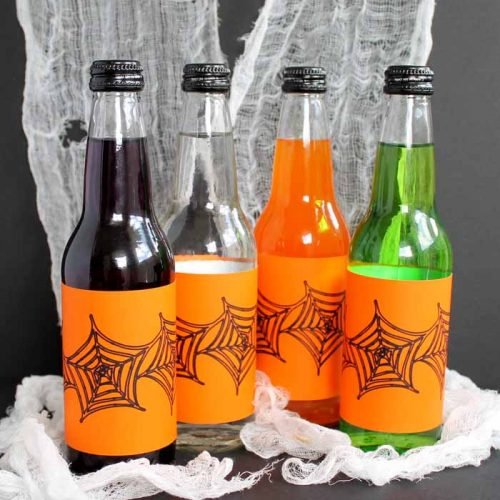 different colors of glass drinks with orange Halloween labels on spider web backdrop