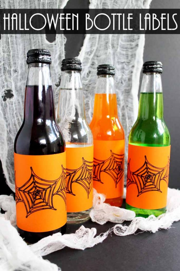 glass bottled drinks with orange labels in front of spider web