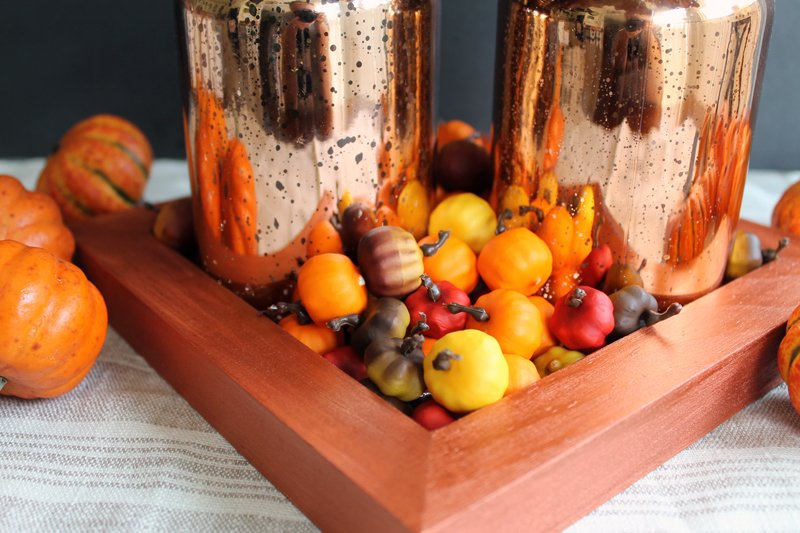 Orange tray with metallic mason jars and small decorative pumpkins