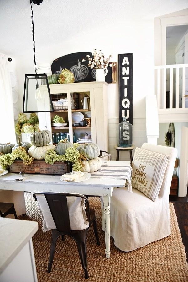 farmhouse style table with pumpkin centerpiece