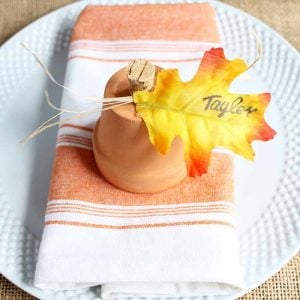 clay pot pumpkins for Thanksgiving place cards on an orange striped kitchen towel