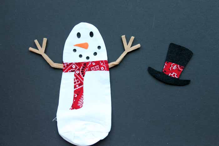 Snowman cut from a cricut with hat beside him on a black background