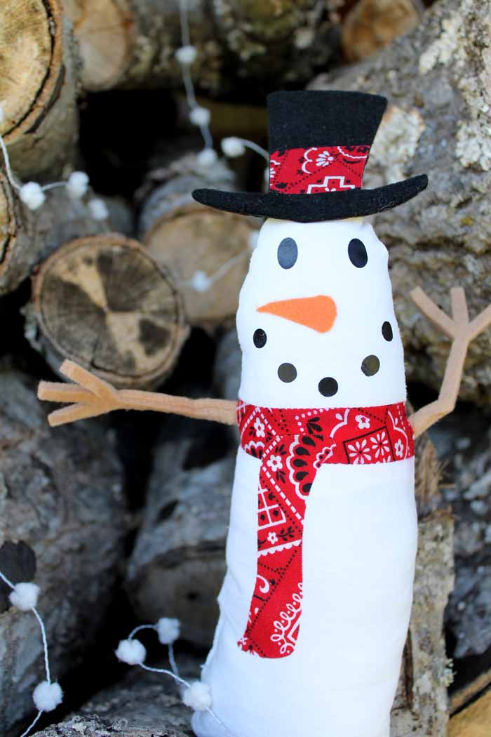 close up of a snowman craft in front of a wooden backdrop