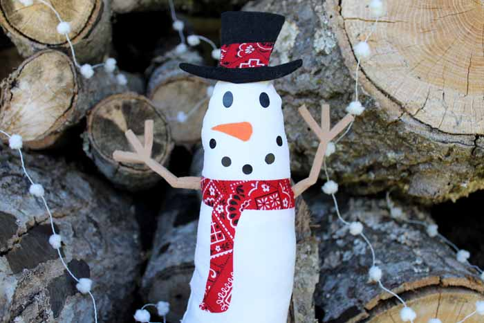Cricut craft snowman in front of wood and pom pom garland