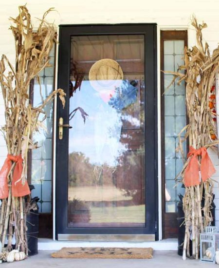 Farmhouse fall front porch with tied corn stalks on each side of a door and mini pumpkins